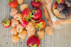 Multicolored raspberries in a glass jar with strawberries on background. Black, red, yellow raspberries in a glass jar with strawberries on a old wooden Stock Photo