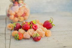 Multicolored raspberries in a glass jar with strawberries on background Royalty Free Stock Photos