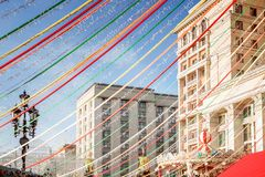 Multicolored ribbons and festive garlands hang on the background of the hotel on Manezh Square. Clear weather at the Pancake Week fair in the center of the royalty free stock photo