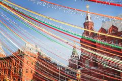 Multicolored ribbons and festive garlands hang on the background of the hotel on Manezh Square. Clear weather at the Pancake Week fair in the center of the stock images