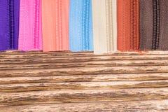 Multicolored ritssluitingen worden opgemaakt op een houten lijst Royalty-vrije Stock Fotografie
