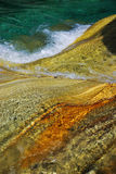 Multicolored rock under the water flowing. Royalty Free Stock Image