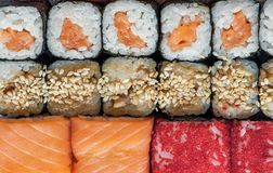 Multicolored rolls and sushi rice, caviar and salmon, are on the table in the background Royalty Free Stock Photography