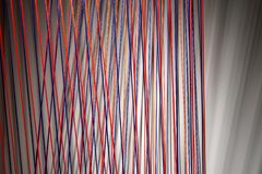 Multicolored ropes lines installation in illuminated interior stock photography