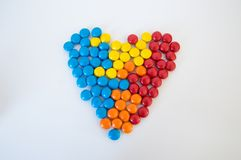 Multicolored round candies dragees laid out in the shape of a heart on a white background stock images