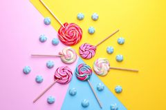 Multicolored round candy and colored lollipops on colored bright backgrounds. Top view stock photos