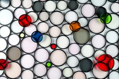 Multicolored round glass photographic filters of various sizes. On a light background stock photo