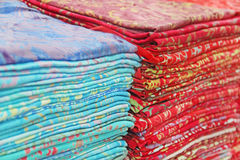 Multicolored scarfs on a shop counter, pile of colorful fabric . Shallow depth of field Stock Images