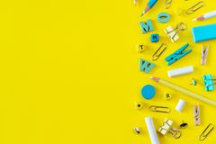 Multicolored school supplies on yellow background with copy space stock images