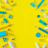 Multicolored school supplies on yellow background with copy space royalty free stock image