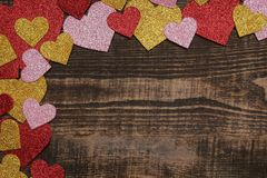 Multicolored shiny hearts on a brown wooden background. frame of hearts, top view with space for text stock image