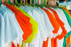 Multicolored shirt clothes hangers in row. Stock Images