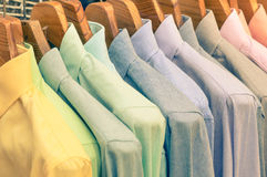 Multicolored shirts hanging on shop rack at weekly flea market. Elegant wardrobe sale concept and alternative retro colors fashion styling Stock Photography