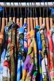 Multicolored shirts ordered on hangers. Many multicolored shirts ordered on wooden hangers Royalty Free Stock Photos