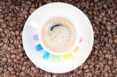 Multicolored slabs of shugar and cup of coffee Royalty Free Stock Photo
