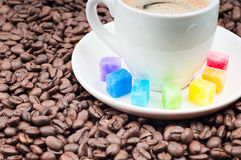 Multicolored slabs of shugar and cup of coffee Royalty Free Stock Photos
