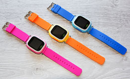 Multicolored Smart watch on a light wooden table. Top view. Multicolored Smart watch on a light wooden table. Top view, close-up Stock Image