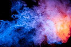Multicolored smoke like cosmic dust of blue, red, magenta and fiery orange on a black is wrapped in rings stock images