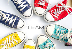 Multicolored sneakers on white background and word `TEAM` concept team work. Stock Photos