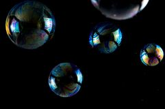 Multicolored soap bubbles close up on a black background, similar to planets.  stock images