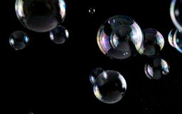 Multicolored soap bubbles close up on a black background, similar to planets.  royalty free stock image