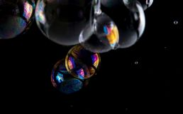 Multicolored soap bubbles close up on a black background, similar to planets.  royalty free stock images
