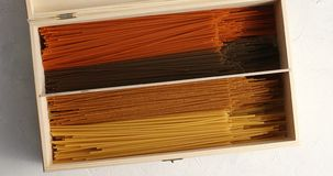 Multicolored spaghetti in wood box Royalty Free Stock Images