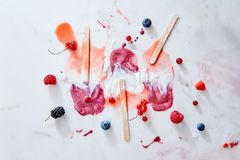 Bright pattern of splashes of ice cream of different fresh berries and sticks on a gray marble background background. Multicolored splashes of melted ice cream stock images