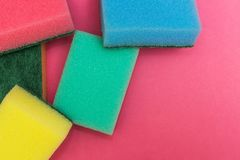 Multicolored sponges on a pink background stock image