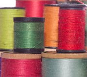 Multicolored Spools Of Sewing Thread. Closeup view of stacked multicolored sewing thread spools Stock Images