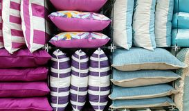 Multicolored stack of cushions. Variety of pink purple blue cushions for sale Royalty Free Stock Photos