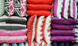 Multicolored stack of cushions. Variety of pink purple and coral colored cushions for sale Stock Photography