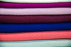 A multicolored stack of fabrics - the fabrics lie on top of each other. The fabric background stock image