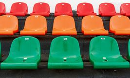 Multicolored stadium seats with numbering. Multicolored plastic seats at the stadium with numbering Stock Photo