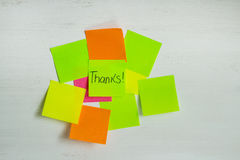 Multicolored stickers on a light wooden surface. Set of multicolored stickers or sheets of paper on a white wooden background. A thank you note on the sticker Stock Photos