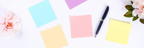 Multicolored sticky note stickers on a white desktop next to a coffee mug and a keyboard. Top view, flat layout.  royalty free stock photography