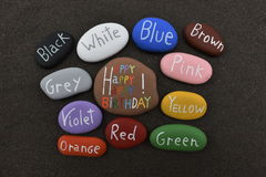 Multicolored stones for a Happy Birthday over black volcanic sand Stock Photo