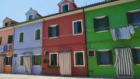 Multicolored street on Burano, famous vivid architecture, tourist attraction. Stock footage stock video footage