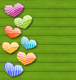 Multicolored striped hearts on green wooden texture for Valentin Stock Photography