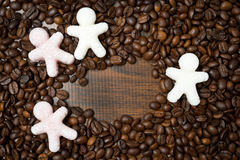 Multicolored sugar in the form of little men on the coffee beans Stock Image