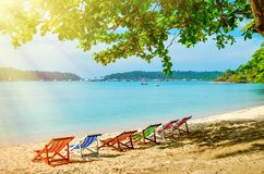 Multicolored sunbeds on a sandy beach in the shade. A hot morning in the tropics. Multicolored sunbeds on a sandy beach in the shade. A hot morning in the Stock Photo