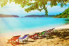 Multicolored sunbeds on a sandy beach in the shade. A hot morning in the tropics.  Stock Photography