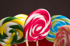 Multicolored sweet candy canes and twirls on wooden sticks. Variety Royalty Free Stock Photo