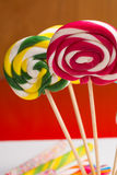 Multicolored sweet candy canes and twirls on wooden sticks. Variety Royalty Free Stock Images