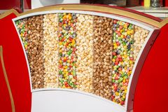 Multicolored sweet popcorn is in a rack under the sun. Background. stock images