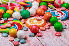 Multicolored sweets and chewing gum. On a wooden table royalty free stock photos