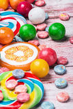 Multicolored sweets and chewing gum on a wooden table Royalty Free Stock Photography