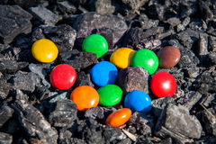 Multicolored sweets in coals. Multicolored sweets in dark charred charcoal Royalty Free Stock Photography