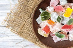 Multicolored sweets, marmalade on a clay plate. Background of burlap. Rustic style. Multicolored sweets, marmalade on a clay plate. Background of burlap Stock Photography