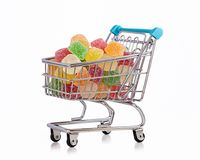 Multicolored sweets in shopping trolley. Miniature shopping trolley full of colored jelly candies Stock Photos
